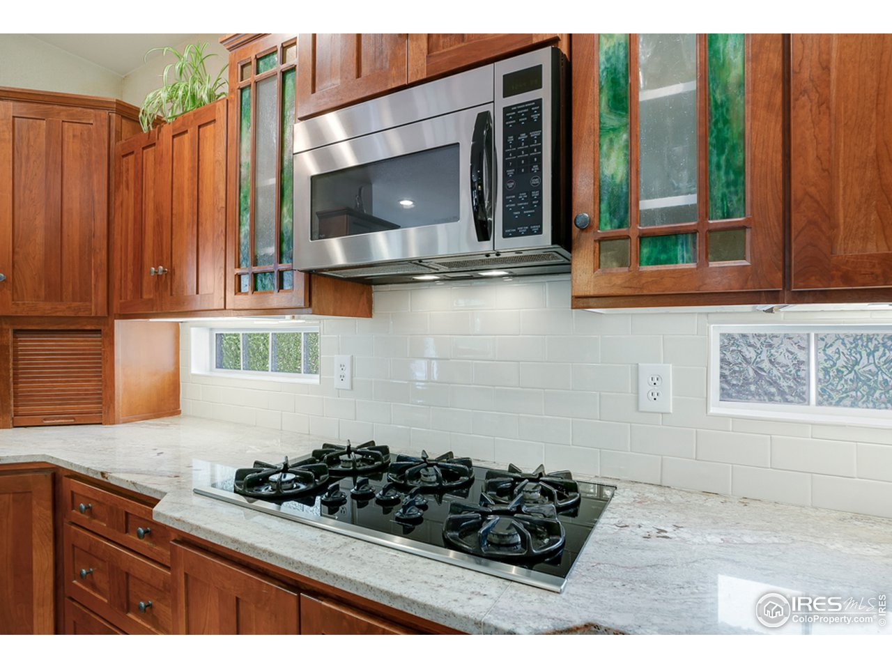 Gas range that vents to the exterior and stunning stained glass detail in the upper cabinets