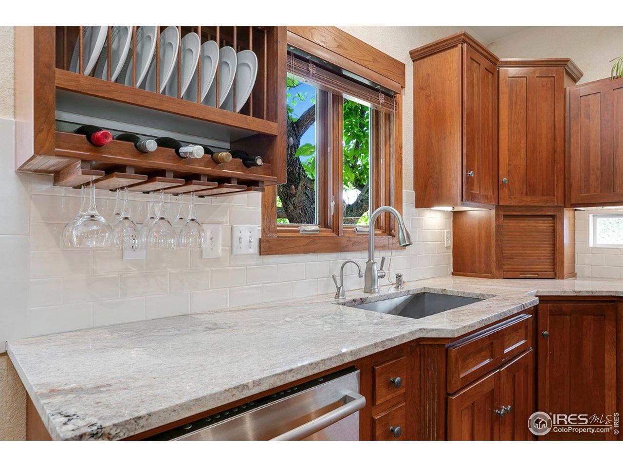 Oversized farmhouse sink overlooking the backyard and beautiful granite countertops