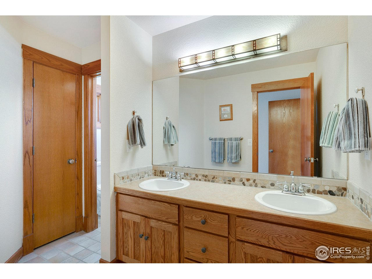 Jack and Jill bathroom w/ double vanity is shared by the upstairs bedrooms