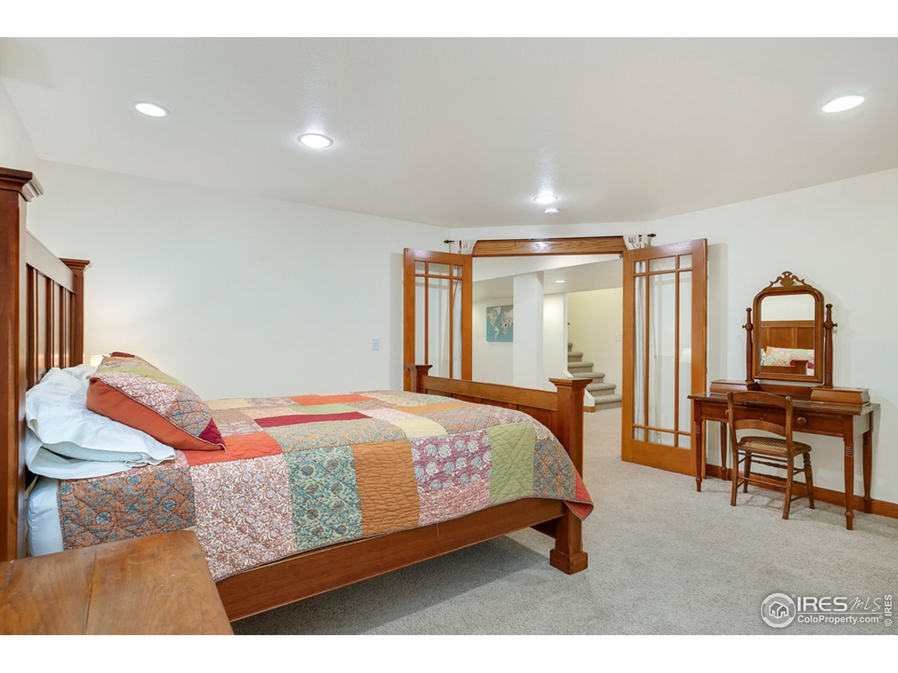4th bedroom in basement features beautiful french doors and huge walk in closet