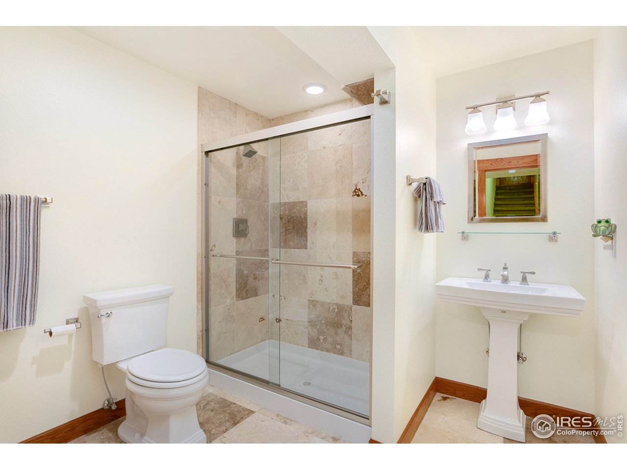 Great sized basement bathroom with Travertine tile