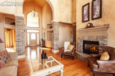 Formal living room with high vaults and attractive stone fireplace