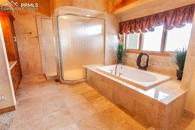 Large jetted tub and shower with marble and travertine tile