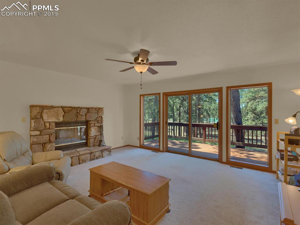 Living Room with wooded views and 2 walk-out lifestyle decks for enjoyment.  LOVE the fireplace!