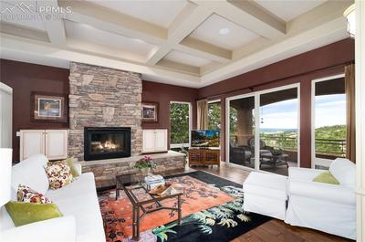 Open family room with pillars, gas stone fireplace