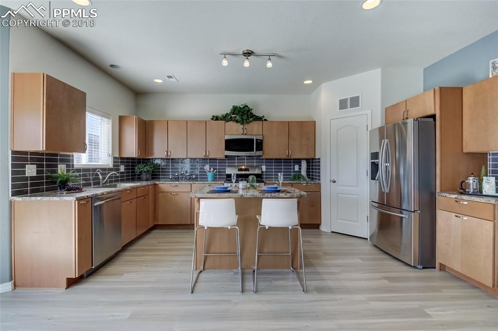 Beautiful kitchen with stainless steel appliances and center island with bar are