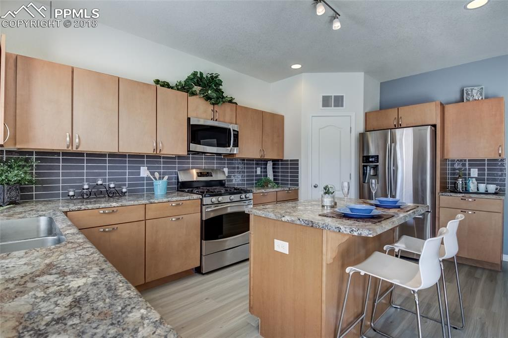 Updated gray tile backsplash, Gas stove, Built-in microwave, pantry and lots of