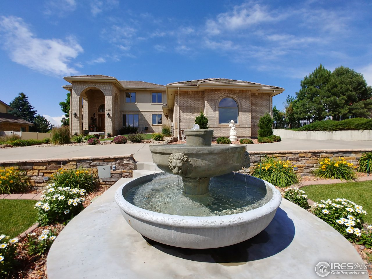 Front yard w/circular drive & 2 water features.