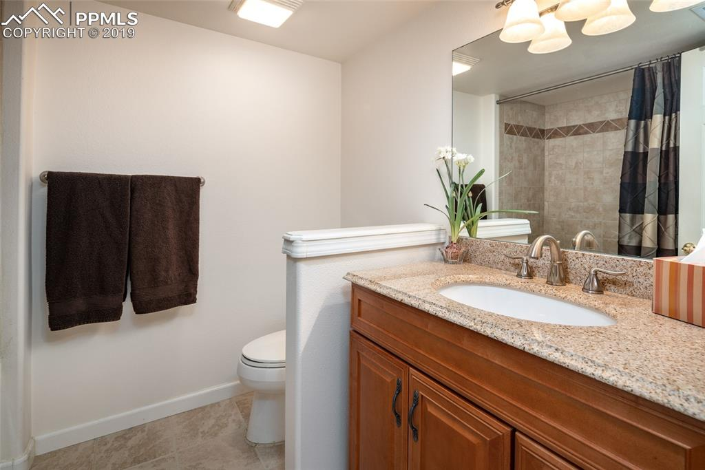 Basement bathroom with beautiful granite counters, tile floors and tiled shower.