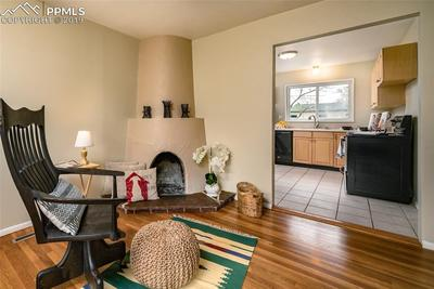 Cozy southwest style fireplace in living room; view to kitchen