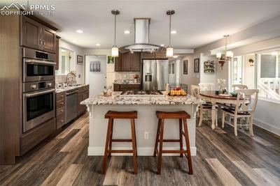 Timeless kitchen with granite counter tops, high-end stainless steel appliances, center island with updated range hood, luxury plank flooring and updated lighting