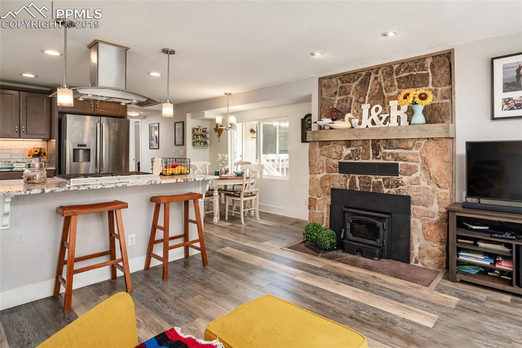 Open concept living, kitchen and dining with cozy fireplace