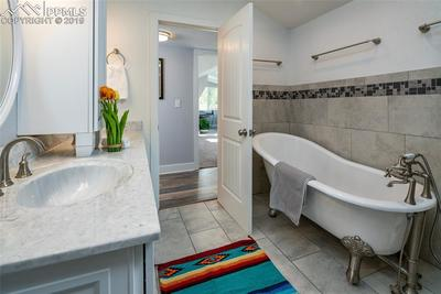 Elegant claw foot tub, updated tile and double vanities