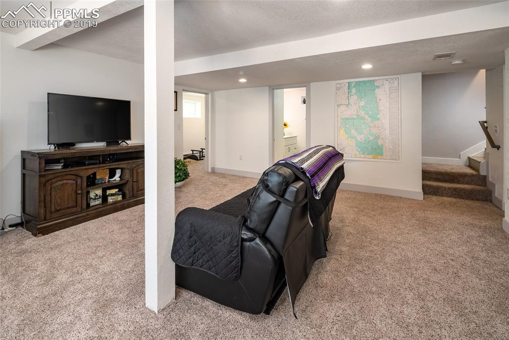 Basement living room with view to exercise room and extra bathroom; newer carpet and fresh paint