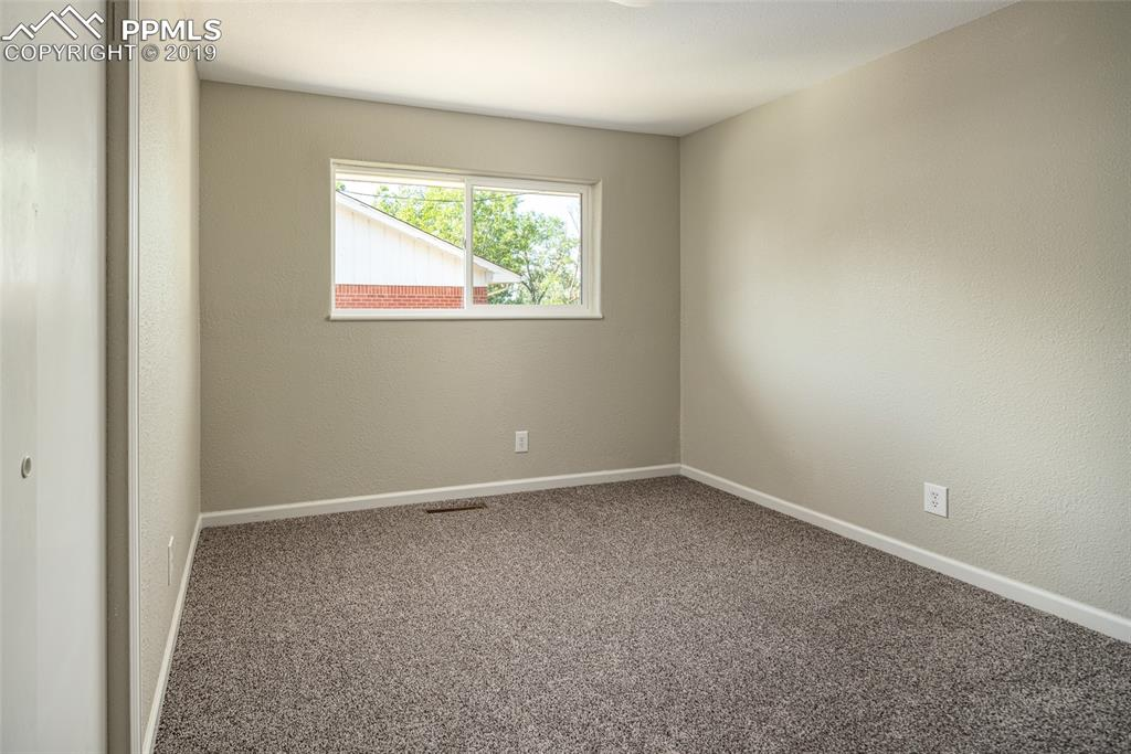 Main level bedroom with brand new flooring, paint and lighting