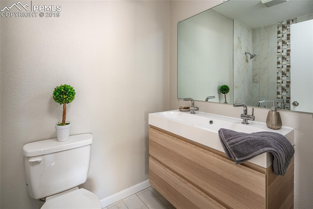 Main level bathroom with brand new paint, tile flooring, double vanities and beautifully tiled shower
