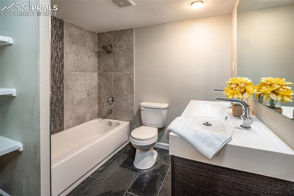 Basement bath with brand new tile flooring, double vanities and beautiful tiled shower