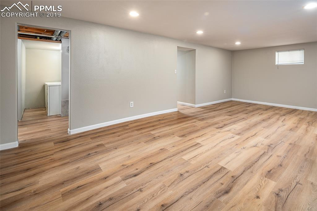 Basement living room with brand new lighting, paint and flooring and attached laundry and storage room
