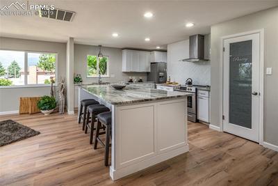 Kitchen with oversized island, granite counters, herringbone subway tile, modern range hood