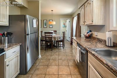 Kitchen and dining room combo with ceramic tile and stainless appliances.