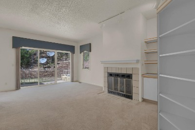 Large living room with built-ins, gas fireplace and walk out to private patio.