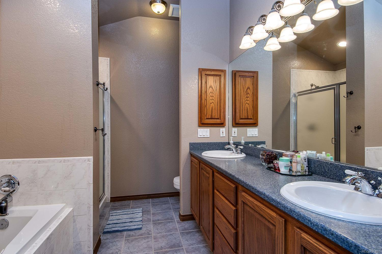 Master bathroom features tiled shower, ceramic tile floors, high ceilings, dual