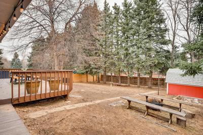 Large backyard with privacy fence, trees & storage shed
