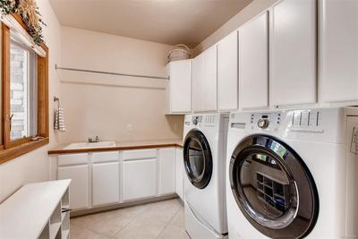 The upstairs laundry room provides a hanging rod, folding space, a utility sink