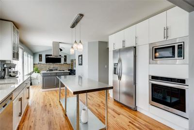 This kitchen has been remodeled - new cabinets, wine fridge, appliances, lighting, glass cabinet doors, and full open view.