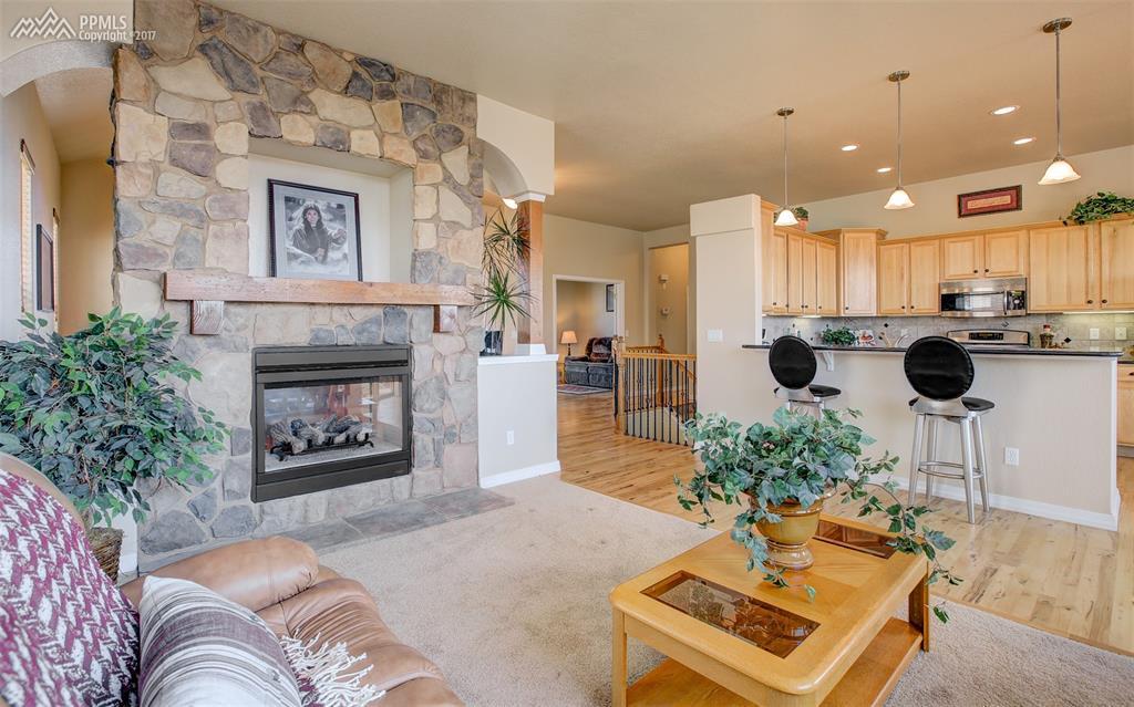 Cozy Pass Through Fireplace With Stone Surround