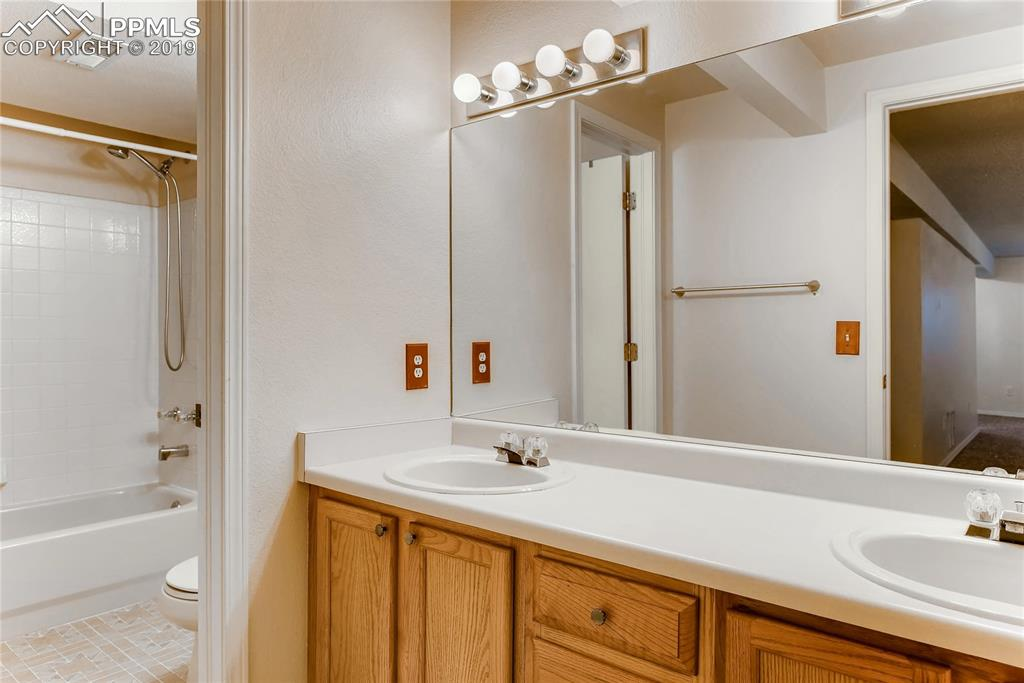 Over-sized full bathroom in the basement with double vanity.