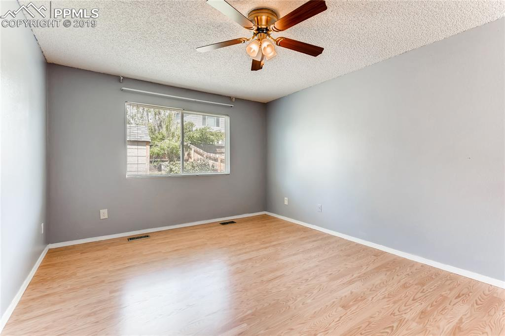 The main level master bedroom features a ceiling fan...