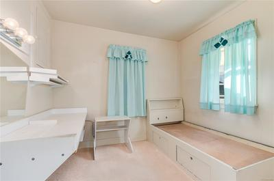Built-in bed frame and vanity offer convenience and comfort to this room.