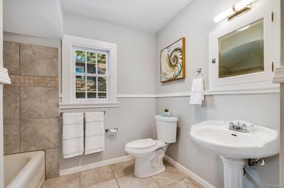 Main floor full bath complete with slate tile flooring & pedestal sink.