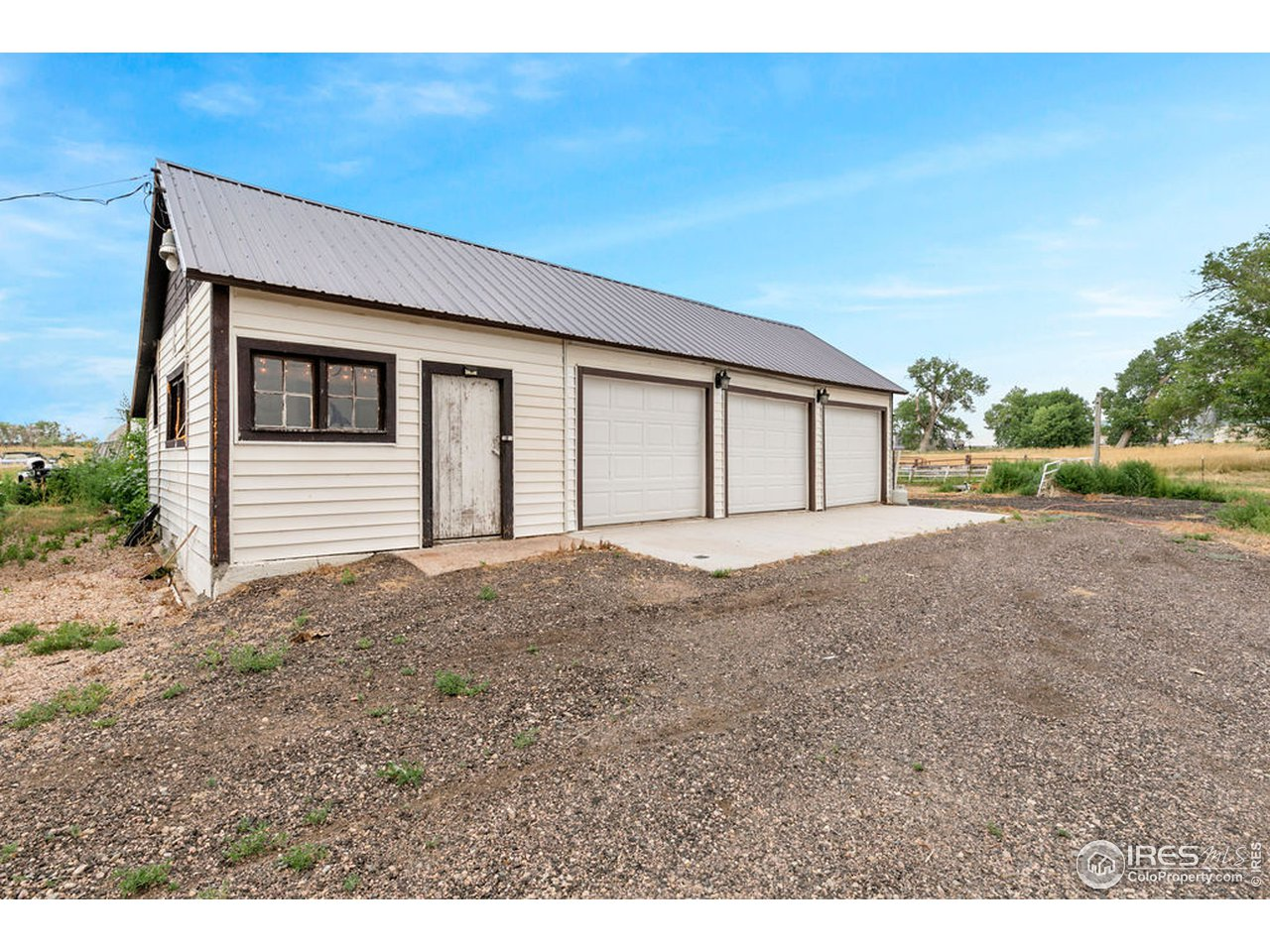 Garage has 3 parking bays on the south side and a double bay on the east for a total of 5 spaces, plus storage and an entertaining space in the west end.  Newer concrete parking apron.  Metal roof was recently replaced.