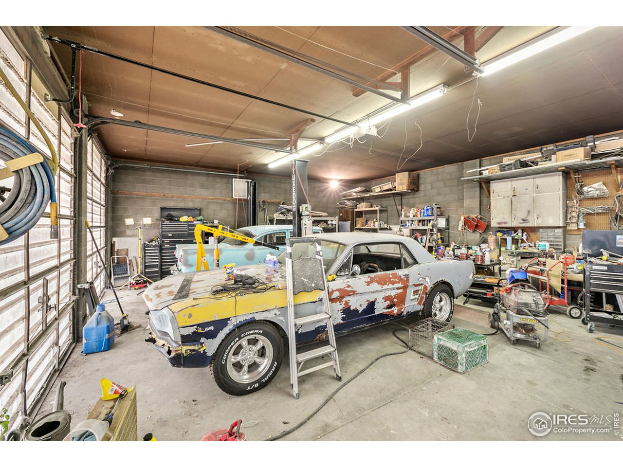 Large, well-lit shop space has plenty of room for projects.  Lift and compressor are not included, but may be for sale separately.  Tools and equipment are not included.