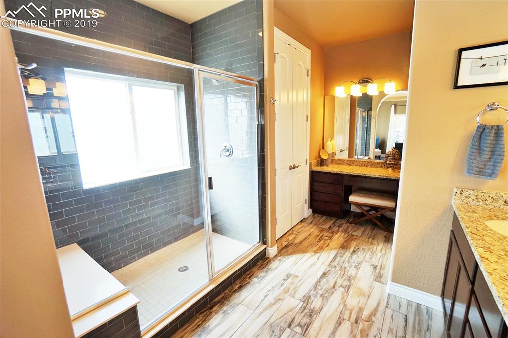 Gorgeous shower has a bench, tiled pan, and full height subway tile.