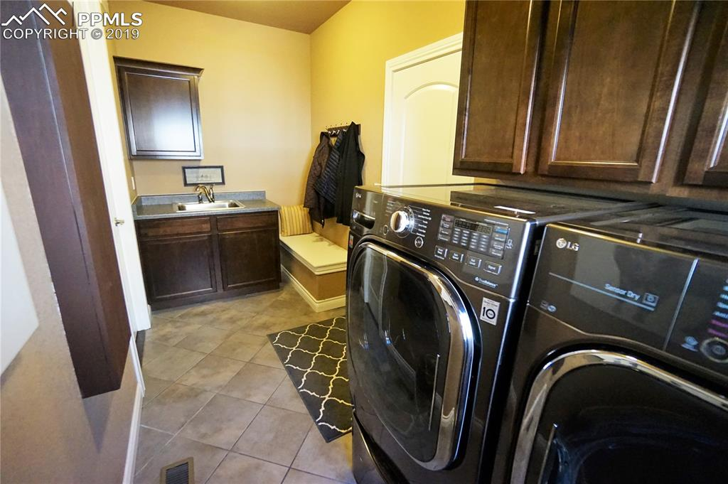 Upgraded laundry include a full assortment of cabinets including a built-in ironing board, bench, and laundry sink.