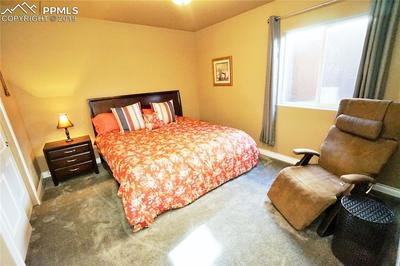 Large basement bedroom has large window and space for furniture.