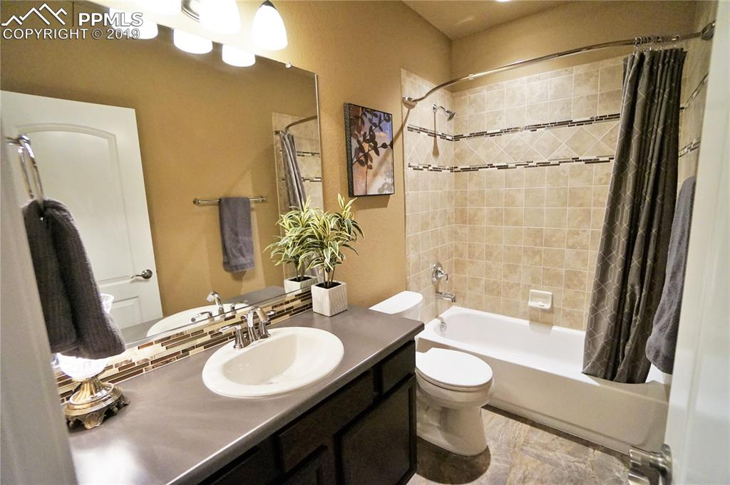 Basement bathroom has custom tile accents and over-sized vanity.
