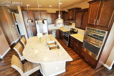 Chef's kitchen has pull-outs, soft-close cabinets, wall oven, pantry cabinets, island, and gas range.