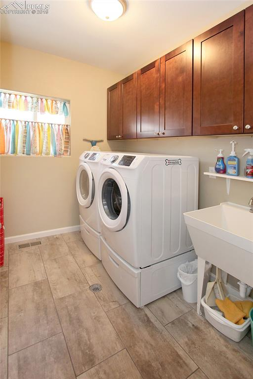 Large laundry room with extra cabinets, sink and Washer & Dryer can stay!