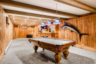 Recreation Room with Bar, Half Bath and Unfinished Storage beyond.