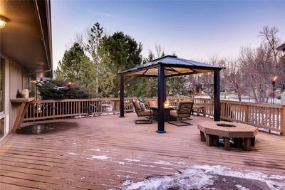 Deck is perfect for entertaining and yard beyond is lined with flowering and fru