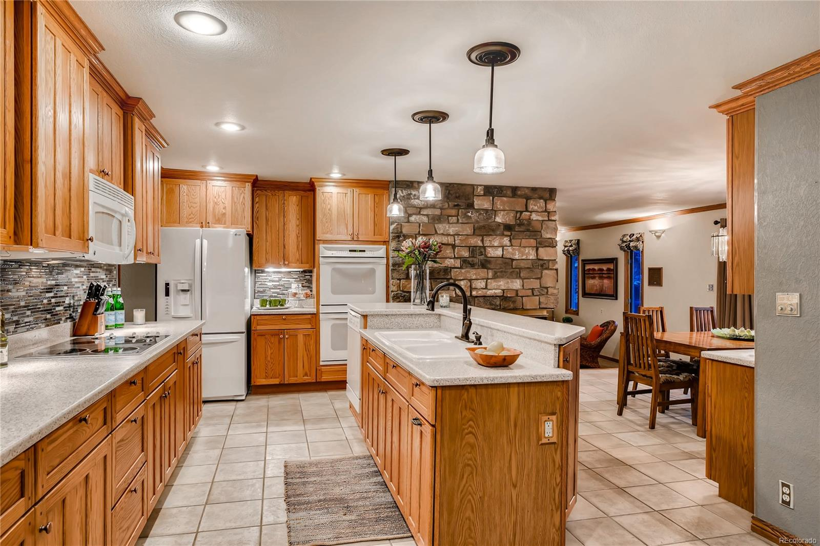 The Kitchen enjoys the shared fireplace with the Living Room and Dining Area.