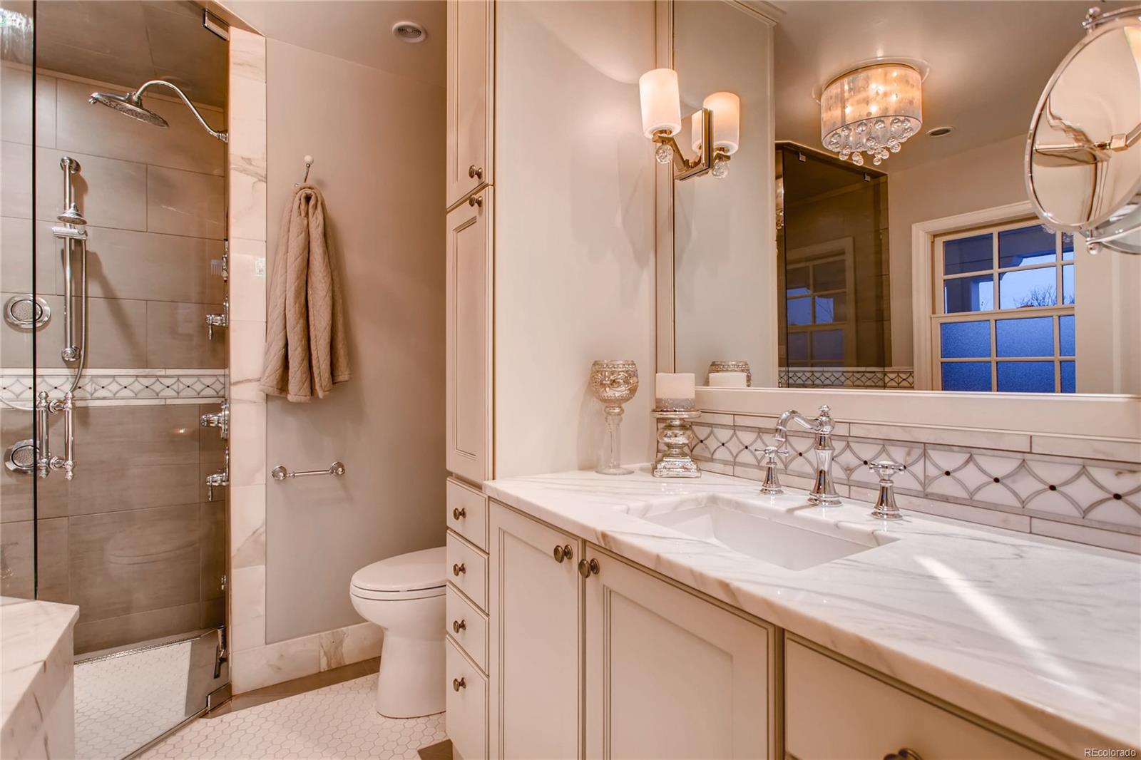 Master Bathroom with marble counters and accents, air bubble tub and steam/rain
