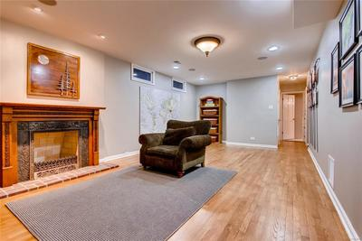 Entertainment Room with Fireplace and hardwood floors in Basement.