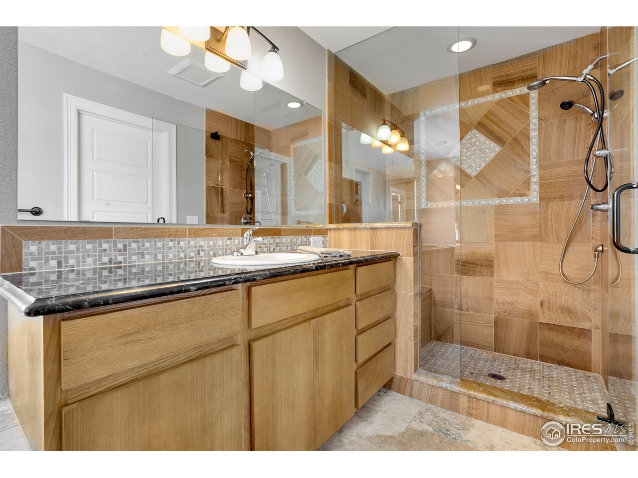 Marble shower with euro-glass offers the feel of a tranquil spa retreat