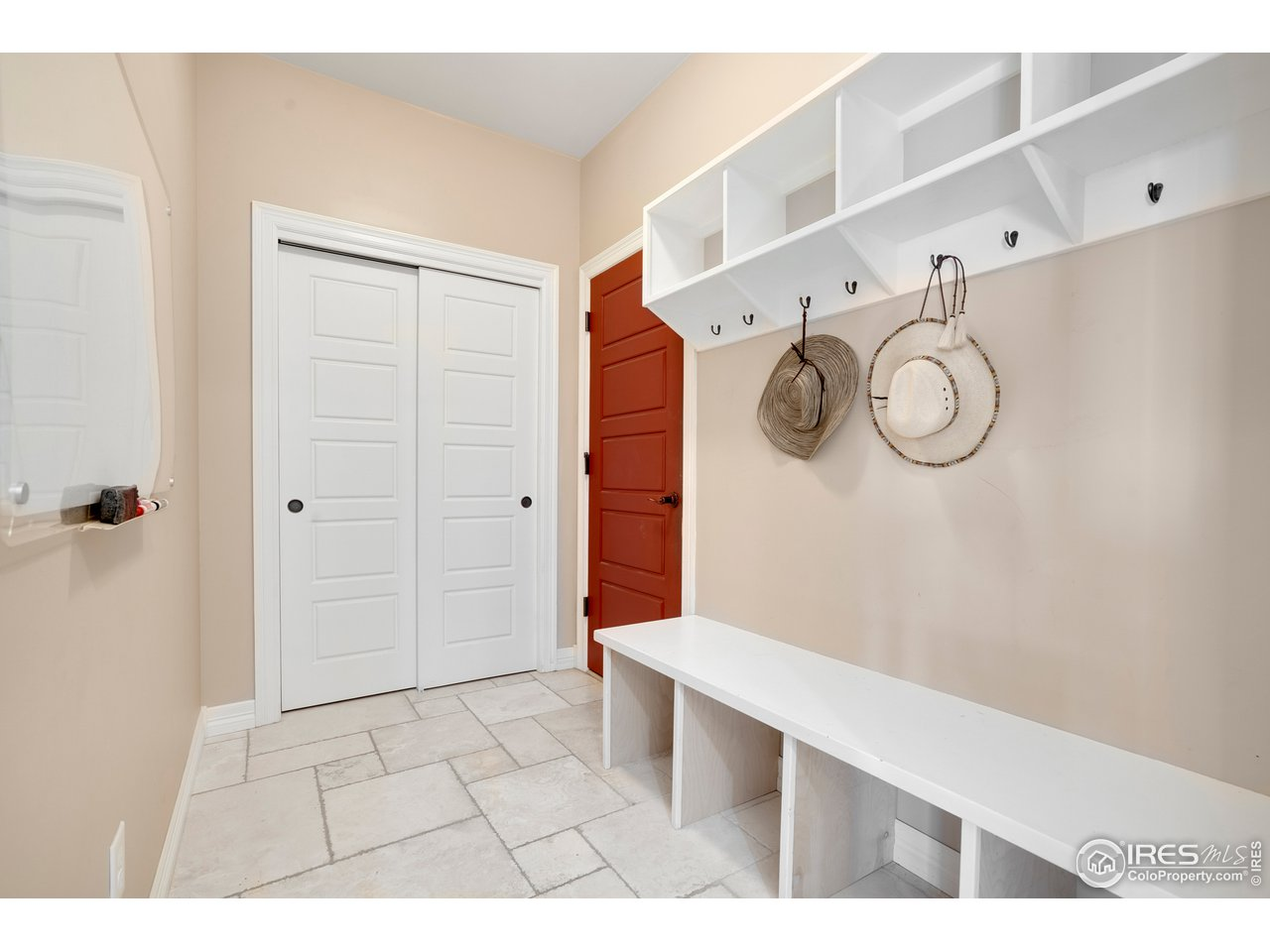 Mudroom with coat closet and service door into garage