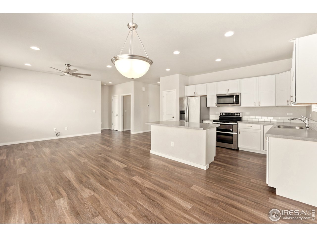 Bright White kitchen with LVP flooring throughout hallway and main living areas